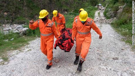 Soldados carregam o corpo de uma vítima do local de um deslizamento de terra em Himachal Pradesh, na Índia, em 11 de agosto.