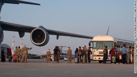 Um grupo de evacuados afegãos deixa uma aeronave C-17 Globemaster III na Base Aérea de Ramstein, Alemanha, 20 de agosto de 2021.