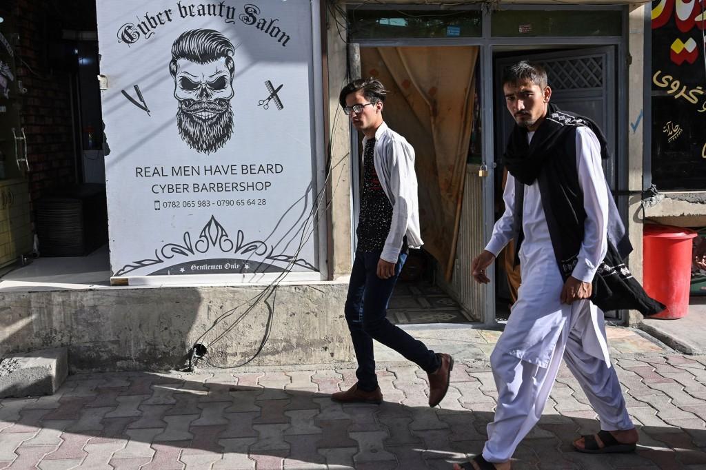 Homens caminham em frente a uma barbearia em Cabul.