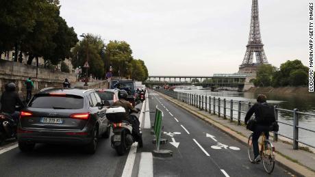 Os ciclistas viajam no trânsito intenso ao longo do Sena, em Paris.